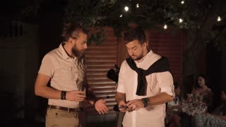 Two men talking and using smartphone together during the party on backyard at night