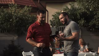 Two men with digital tablet standing in garden and talking and laugh