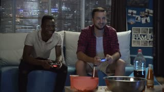 Two multiethnic men gathering on sofa at home and playing videogame with gamepads