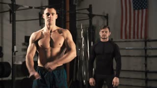 Two muscular brutal athletic men standing with hands crossed in gym and looking at camera confidently.