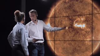 Two scientists discuss the trajectory of the shadow of the solar eclipse moving along the surface of the Earth. Elements of this image furnished by NASA