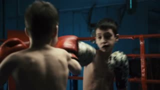 Two shirtless boys wearing gloves and fighting on ring practicing Thai box looking serious and determined.
