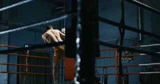 Two shirtless men in boxing gloves fighting and training Thai box moving on square ring.