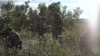 Two soldiers sitting in nature and using map and gps tracker for navigation