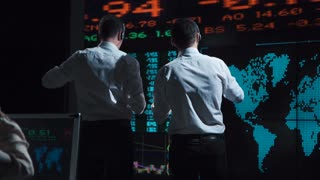Two stock brokers in front of a live global market feed in a bustling, futuristic office
