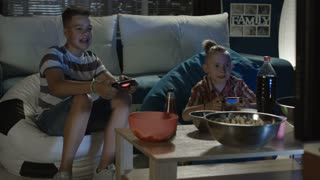 Two teenagers spending time at home playing videogame with gamepad having snacks while sitting on sofa then one player win and start to laugh and tease other player his friend