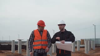Two workers move on the incomplete building site and discuss smiling. Possibly it is the end of the working day and they go home