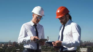Two young male architects or engineers standing in their hardhats on the skyline above a city having a meeting and discussion as they take notes then shaking hands
