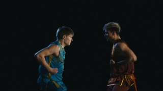 Two young men training wushu martial art against dark background