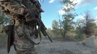 Unrecognizable military man with firearms walking on battlefield