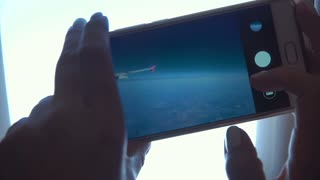 Unrecognizable woman taking shots with smartphone through illuminator in airplane