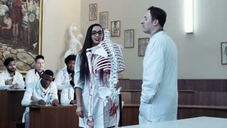 Video clip of young woman student weared eyeglasses in anatomy class with teacher and skeleton dummy. 4K middle shot