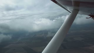 View from a small plane of grey storm clouds over an open landscape below in a concept of flying and aviation