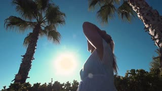 View from below young woman in sunglasses looking up to palms and adjusting hair
