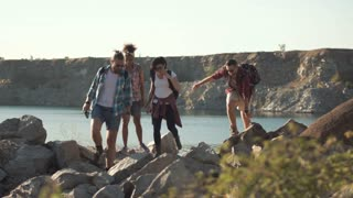 View of group of people walking on rocks and helping each other while backpacking in summer. Slow motion