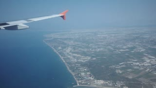View to wing of airplane flying in blue cloudless sky