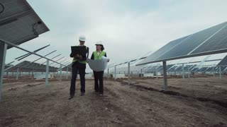 Wide angle the engineers meets workers and start walking between the solar energy panels and discussing the blueprint