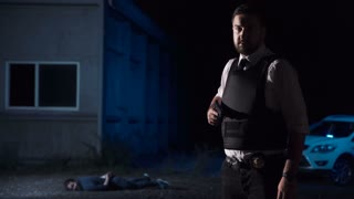 Wide portrait of an effective police officer wearing bullet proof vest while looking at camera after catching a suspect in the suburbs at night