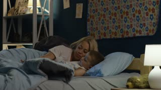 Woman embracing and putting little boy to sleep while lying together on bed and covering with blanket