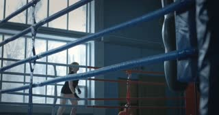 Woman in sportswear and gloves working out on ring practicing techniques of box.