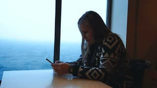 Woman in sweater sitting at table in cabin of sailing contemporary ferryboat and browsing smartphone with view of cold sea behind window