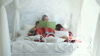 Woman lying on bed with children and reading book at home