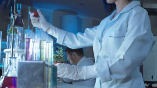 Woman scientist in gloves dropping chemicals in pot with plant while working in lab