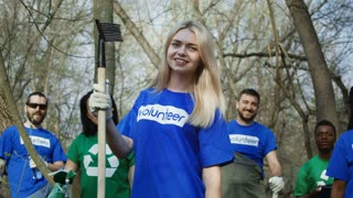 Woman standing with smiling multiethnic friends in shirts of volunteers working in team in forest.