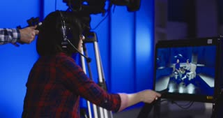 Woman wearing a headset sitting behind a monitor with the cameraman during production giving instructions in a newsroom gesturing and pointing
