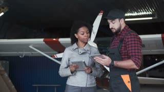 Worker man and woman standing with tablet and talking in hangar