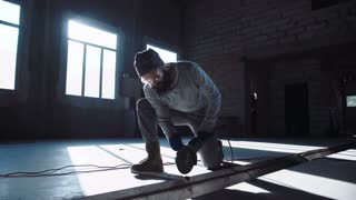 Worker man cutting metal part with angle grinder and looking at camera