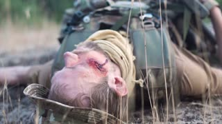Wounded man in military uniform lying on ground with eyes closed