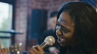 Young African-American woman holding microphone and singing into it with deep feelings and eyes closed