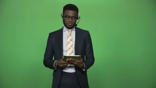 Young african black male in formal suit wearing headset and holding tablet ready for customer supporting in in call center then turn to camera looking and smile