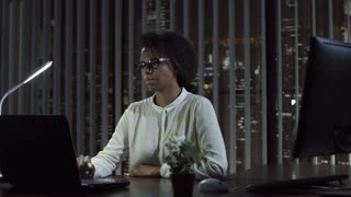 Young black woman sitting and talking at laptop in office at night