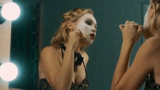 Young blond woman in dressing room doing stage makeup with white paint before performance