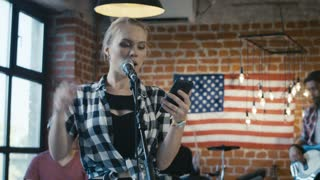 Young casual girl watching lyrics in smartphone and singing into microphone on stage with group