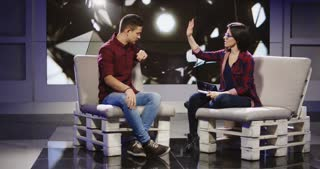 Young confident and relaxed man and woman taking participation in television show sitting in modern illuminated studio and having talk