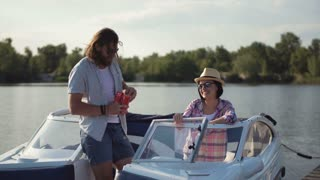 Young couple toasting each other with cans of beer as they relax in the evening on a lake in a motorboat while enjoying their summer vacation