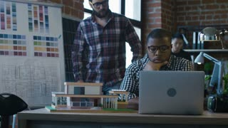 Young diverse man in glasses sitting at working desk and discussing model of futuristic accommodation in office