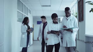 Young diverse medical students in hospital corridor talking together