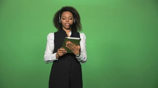 Young female in formal suit wearing headset and holding tablet ready for customer supporting in in call center