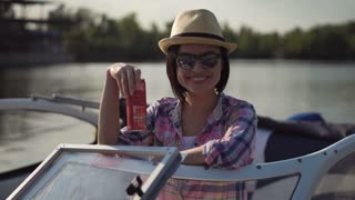 Young girl in straw hat taking off sunglasses while smiling at camera on boat with drink holding in hand