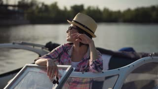 Young girl in straw hat taking off sunglasses while smiling at camera on boat