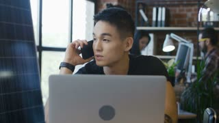 Young handsome Korean man having phone call while sitting at working desk in office with laptop
