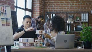 Young Korean man and African-American woman constructing futuristic living house with alternative supplies while sitting at table