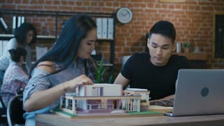 Young Korean man and woman constructing futuristic living house with alternative supplies while sitting at table