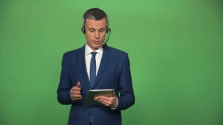 Young male in formal suit wearing headset and holding tablet ready for customer supporting in in call center