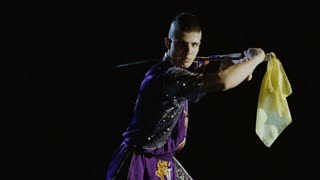 Young man training wushu martial art with sword against black background