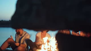 Young multiracial people gathering around campfire on shore and grilling sausages in twilight